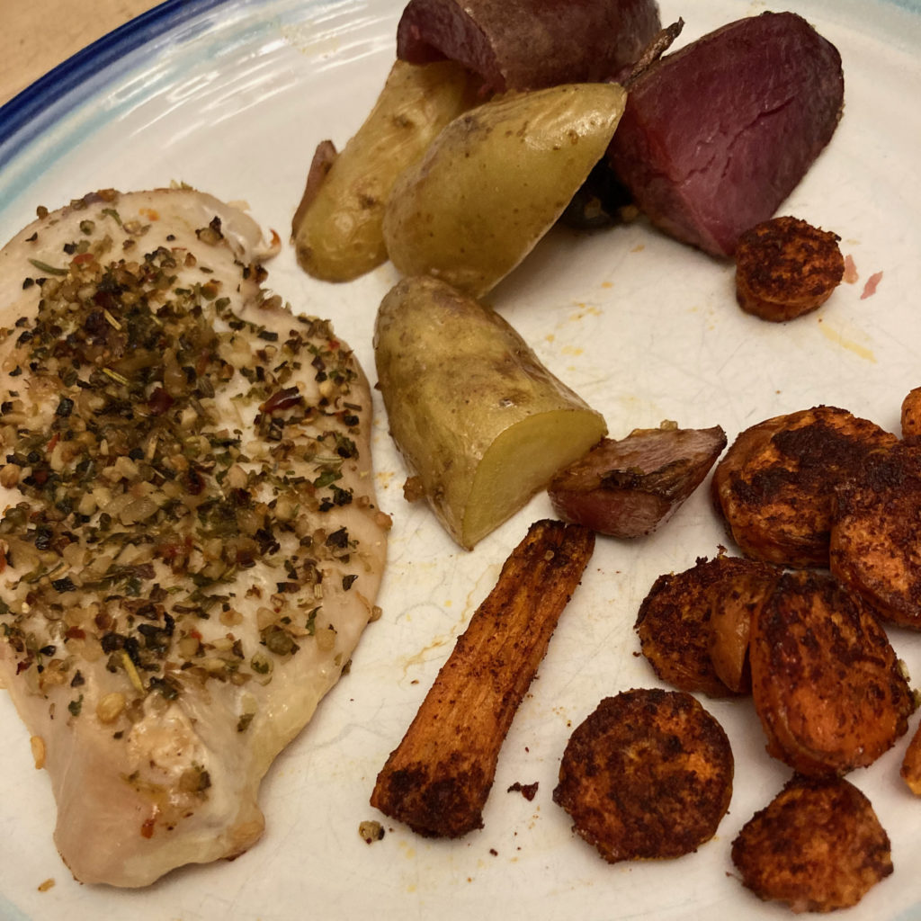Roasted chicken, potatoes, and carrots on a white plate with blue trim.